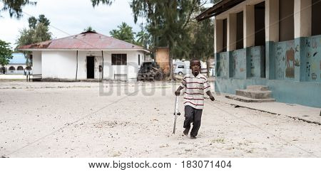 Zanzibar, Tanzania - July 14, 2016: Child of Zanzibar playing with a wheel, dirty-looking, shacks on the background