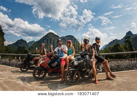 19 April 2017 West side Ho Chi Minh Trail, near Phong Nha. Tourists on Motor Scooter Along Ho Chi Minh trail on hill danger terrain with mountain pass.