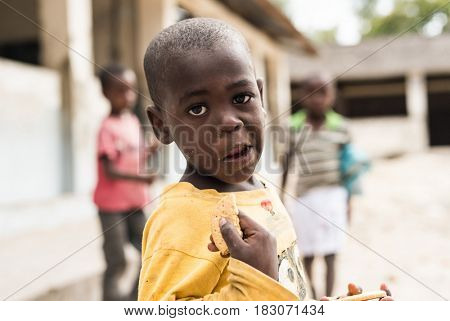 Zanzibar, Tanzania - July 14, 2016: Local kid in a yellow shirt, eating cookie in Zanzibar, Tanzania
