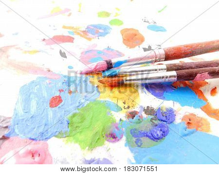 Palette of paint with many colors and three brushes.