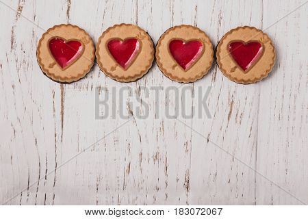 Four cookies with a heart on a wooden table
