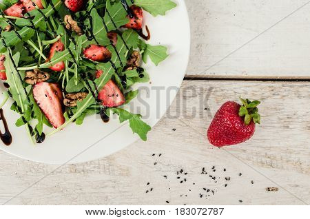 Fresh salad with arugula strawberries nuts black sesame seeds and balsamic glasse sauce served on white plate on rustic wooden table. Healthy organic diet food concept. Top view. Copy space.