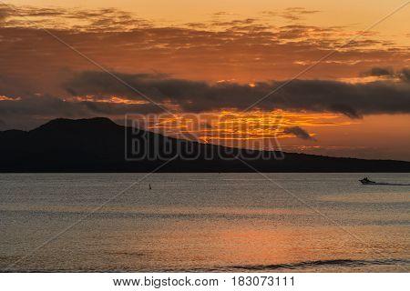 Auckland New Zealand - March 2 2017: Sunrise over Rangitoto Volcano shot from Tapapuna Beach in the Hauraki Gulf. Shot 1 of 4. Fire lines in sky among dark clouds. Black volcano. Blue-gray ocean water reflects orange sky.