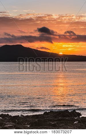 Auckland New Zealand - March 2 2017: Sunrise over Rangitoto Volcano shot from Tapapuna Beach in the Hauraki Gulf. Shot 2 of 4. Half sun Black volcano. Blue-gray ocean water with orange reflections