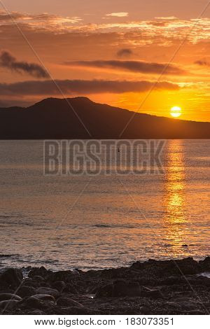 Auckland New Zealand - March 2 2017: Sunrise over Rangitoto Volcano shot from Tapapuna Beach in the Hauraki Gulf. Shot 4 of 4. Full sun Black volcano. Blue-gray ocean water with orange reflections.