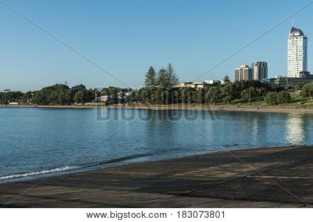 Auckland New Zealand - March 2 2017: Black volcanic south shore of Tapapuna Beach shows park highrise and canoe rowers under blue sky with reflecting sea water.