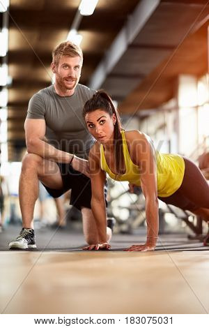 Female and male on exhausting training in gym