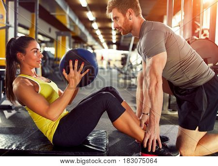Female exercising six pack muscles with partner in gym