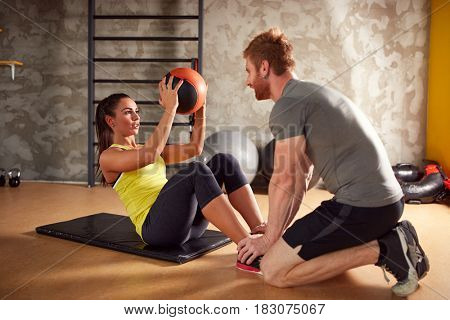 Sporty woman exercising six packs with ball in gym