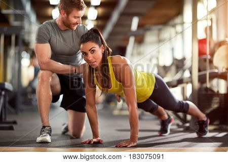 Girl doing pushups with trainer's helps in fitness club