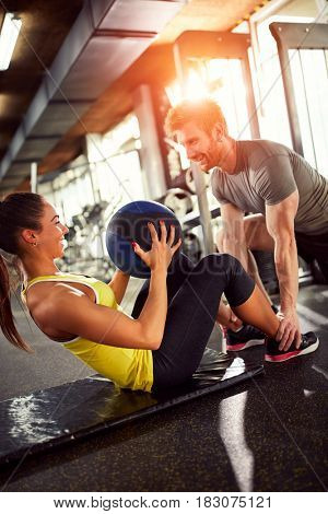 Girl with trainer on training in gym