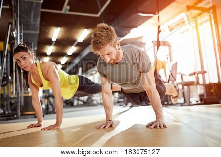Woman with coach doing hard exercise in gym