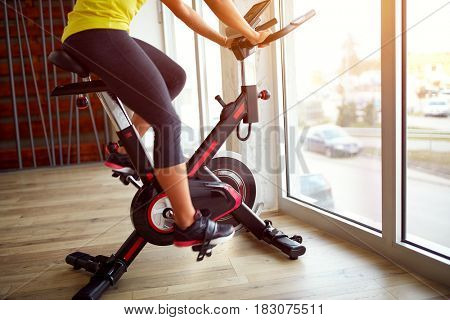 Woman in gym exercise on sport bicycle on sunny day