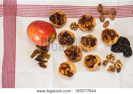 Magnificent portioned tartlet cakes with filling nuts and dried fruits. Professional baking