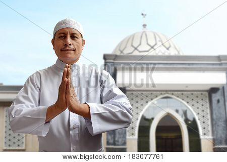 Old muslim man smiling and greeting outside mosque