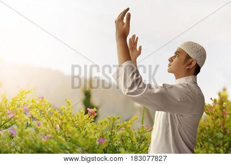 Muslim man praying to God in a garden