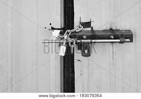 Locked padlock and chained on metal sheet gate black and white tone