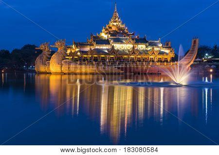 Golden Karaweik palace on Kandawgyi lake looks like an ancient royal barge. Twilight time. Yangon, Myanmar