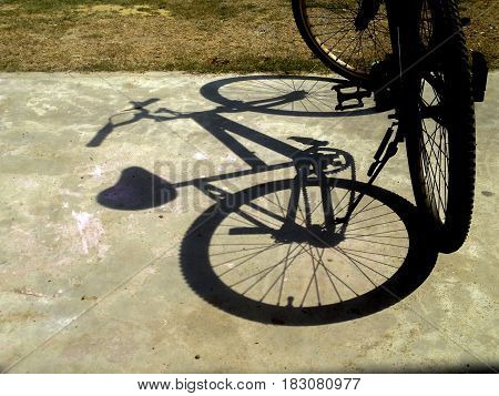 a bicycle shadow on the ground .