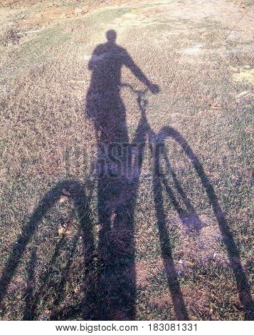 man with bicycle shadow on ground .