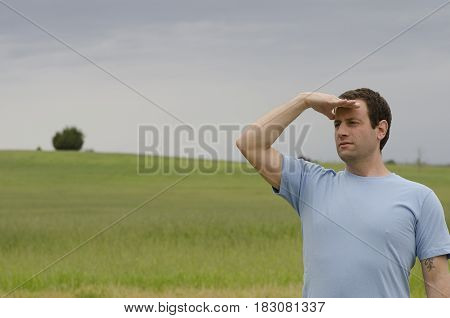 Man looking out to what the future holds in an open field of green grass.