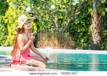 Asian young woman Living by the pool in the summer in the morning.