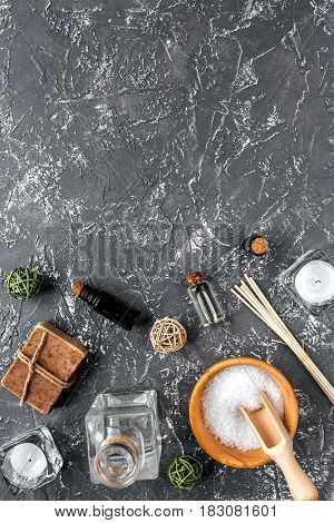 spa cosmetics set with soap, salt, oil on dark desk background top view space for text