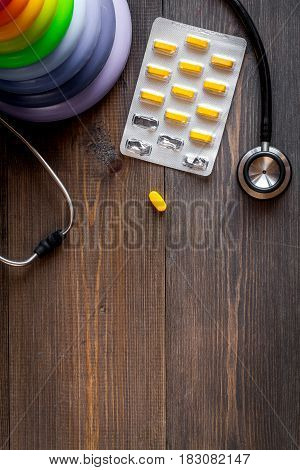 Pediatrics equipment with toys, medicine, stethoscope on wooden table background top view space for text