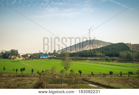 Tianjin, China - Nov 1, 2016: Image captured on High Speed Rail (HSR) from Tianjin to Shanghai, passing countryside with a wind generator and other high-rise structures. Average speed: 300 km/h.