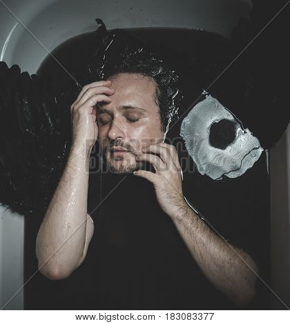 Satan, Fallen angel, man in a bathtub with black water and wings, submerged, depression, loss