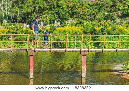 Father And Son Are Walking Along The Bridge Over The Pond. Traveling With Children Concept