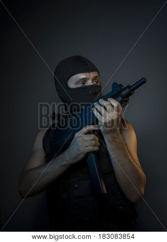 Soldier Military, Terrorist, a man dressed in a bulletproof vest and balaclava, is armed with pistols and machine guns