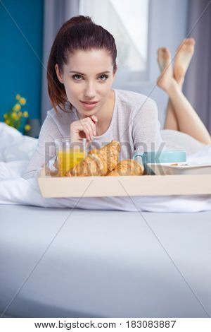 young beauty  woman having breakfast in bed early sunny morning