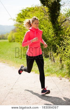 Young Woman In Pink And Black Dress Runs Cross Country On A Warm Spring Day