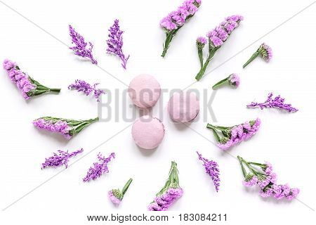 spring woman breakfast with macaroons and mauve flowers white background top view