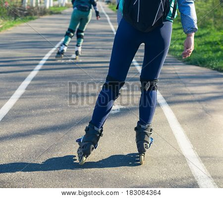 Two girls on roller skates ride along the road. Sport girls. One girl is ahead of the other.