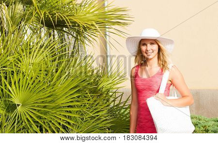 Young Stilish Woman In Pink Short Summer Dress Walks Around A Costal City On Her Vacations