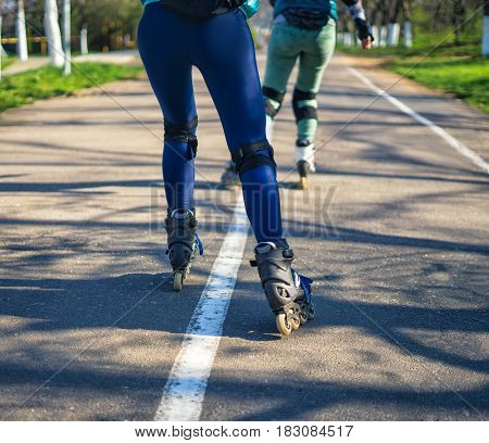 Competitions in roller skating. Two girls on roller skates ride along the road . Sport girls. View of legs