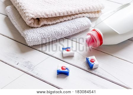 Bath towels stack with detergent plastic bottle in laundry on light table background