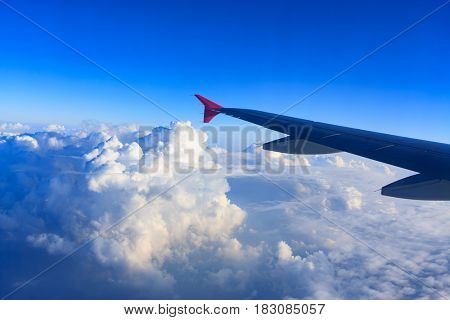 Airplane wing flying above the clouds at sunset