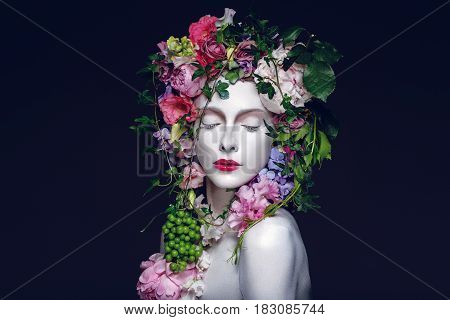 Beautiful young pale white woman with different flowers on head. Flower queen. Eyes closed. Beauty shot on black background.