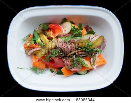 Appetizer made of roast beef and vegetables in enamel plate isolated on black background