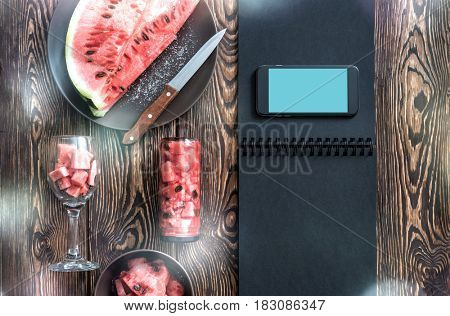 Template of the smartphone next to watermelon slices, with knife and glass. Clipping path
