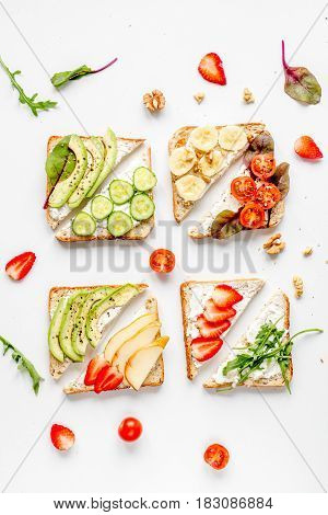 lunch with triangle sandwiches with fruits and vegetables on white table background top view