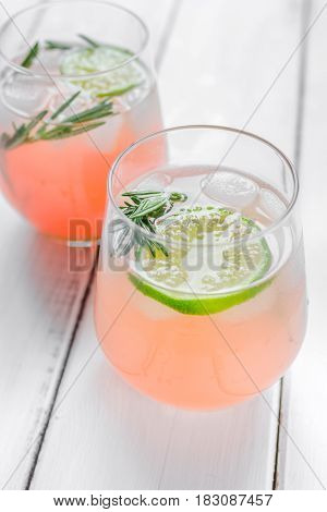 fitness cocktail in glass with cut lime and fresh rosemary on white wooden table background