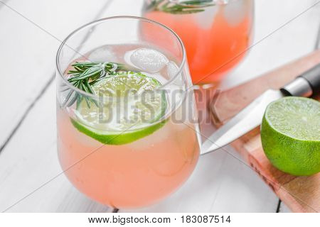 vegetable smoothie with lime pieces and fresh rosemary in glass on white table background