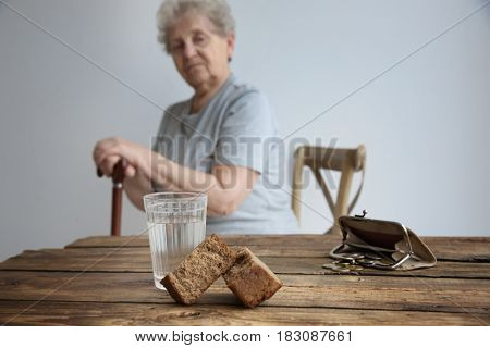 Bread, glass of water, purse and coins with blurred senior woman on background. Poverty concept