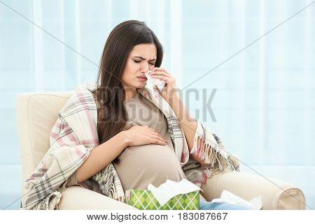 Pregnant woman with allergy sitting on armchair at home