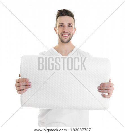 Young man with orthopedic pillow on white background. Healthy posture concept