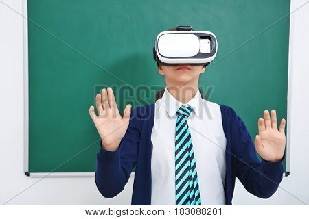 Schoolgirl with virtual reality glasses in classroom